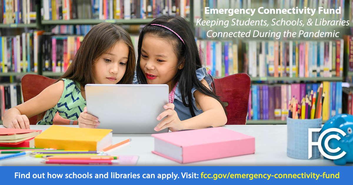 Emergency Connectivity Fund - two girls at table in library looking at a tablet computer