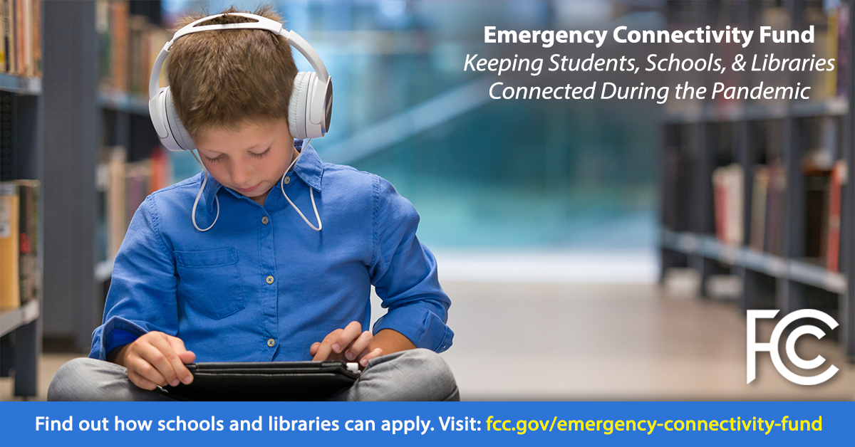 Emergency Connectivity Fund - boy with headphones sitting on library floor looking at a tablet computer