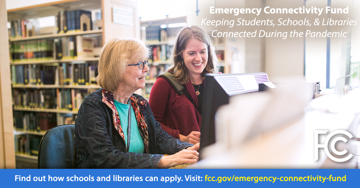 Emergency Connectivity Fund - senior woman and young woman at a library table looking at a computer