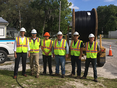 Chairman Pai with workers wearing reflective vests and hard hats in front of giant spool of fiber cable at a broadband access site in Gadsden County, Florida as part of his Digital Opportunity Tour to highlight the FCC's work to close the digital divide. Click for full size image.