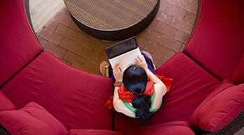 Top down view of young woman with laptop sitting on a large circular red sofa in front of a circular coffee table.