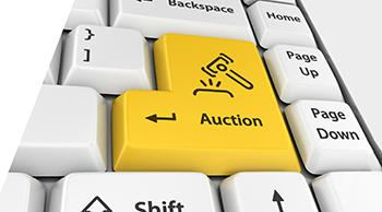 white computer keyboard with yellow key showing a gavel icon and the word Auction