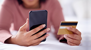 Woman holding and looking at smartphone and credit card.