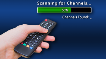 hand holding TV remote in front of progress bar scanning for channels