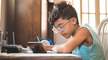 boy with glasses at a desk holding a pen looking at a phone