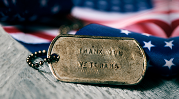 Thank You Veterans engraved on dog tags on U.S. flag background